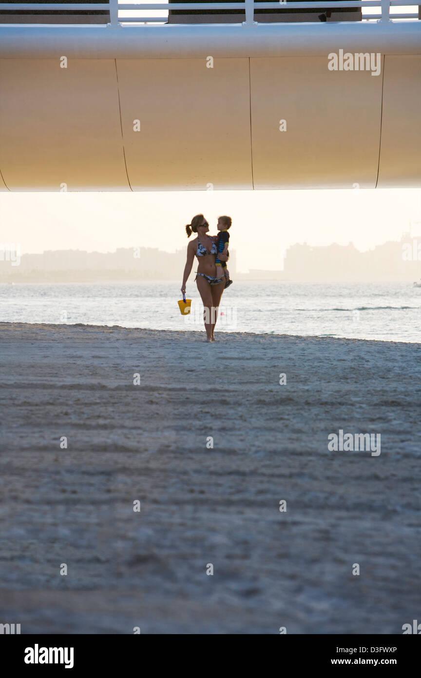 Woman and infant walk along on the beach beneath the access roadway to the Burj Al Arab seven star hotel in Dubai Stock Photo