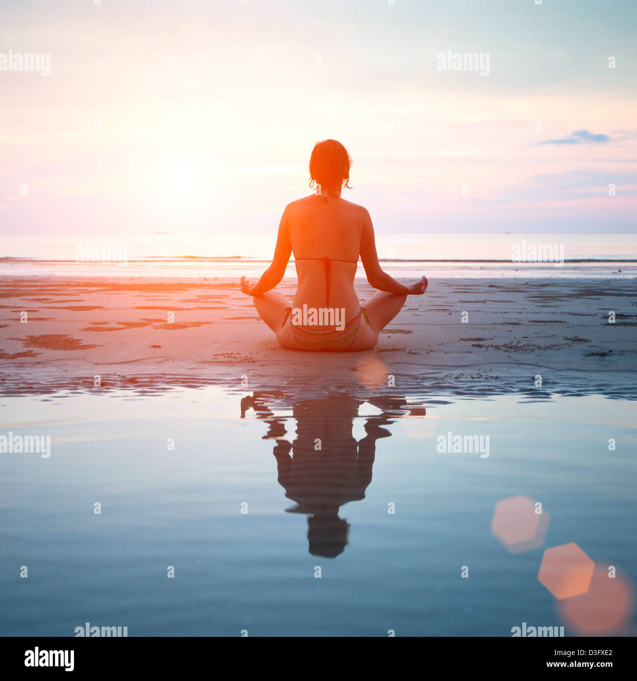 Woman practicing yoga on the beach at sunset, with reflection in water. - Stock Image