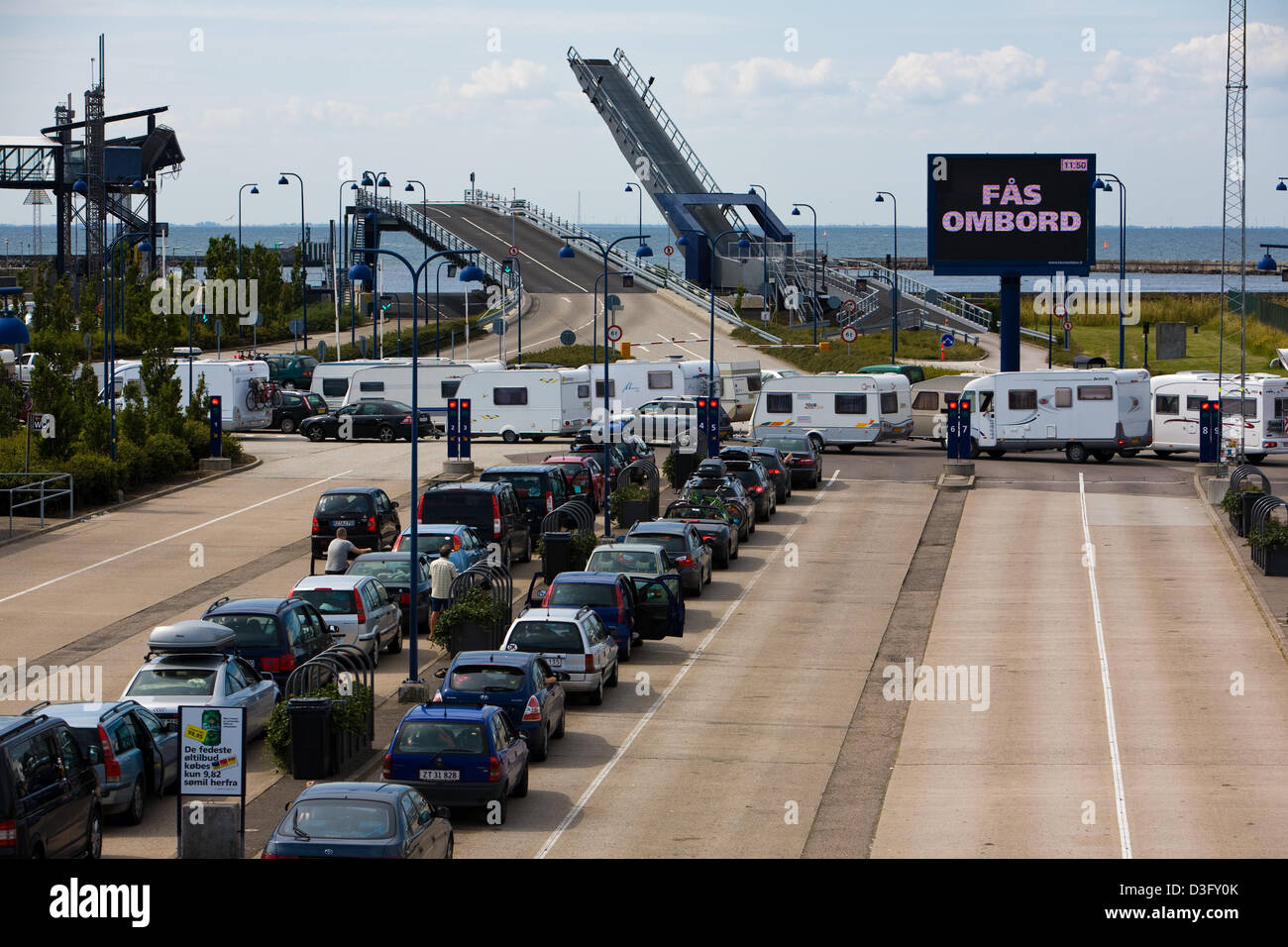 Cars standing in line and waiting to baord the ferry in the harbour of Roedbyhavn in Denmark with destination Puttgarden - Stock Image