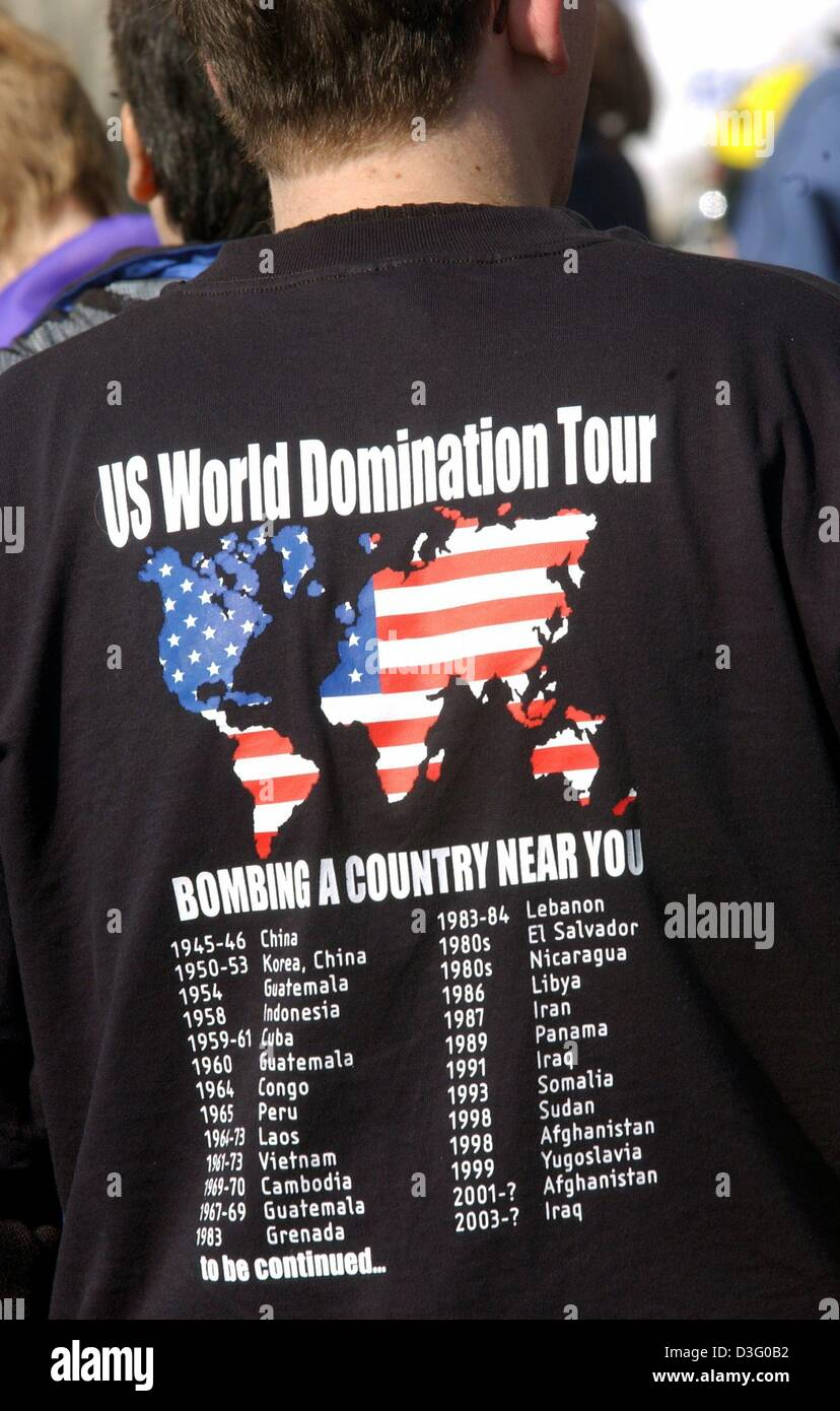 (dpa) - An objector wears a T-shirt which reads 'US World Domination Tour, bombarding a country near you' during Stock Photo