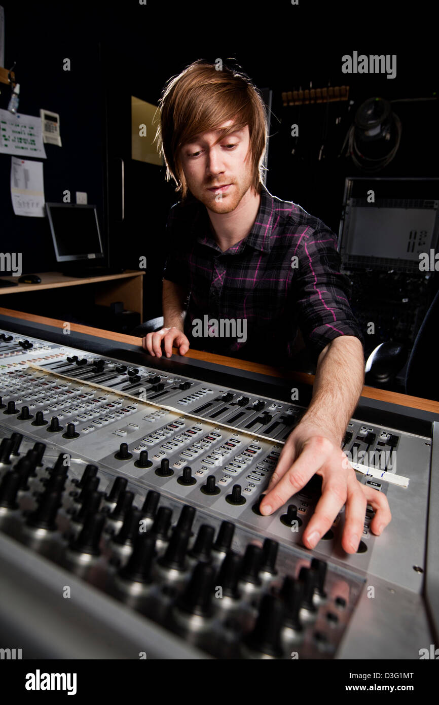 Sound engineer using a studio mixing desk. Selective focus on Sound desk. - Stock Image
