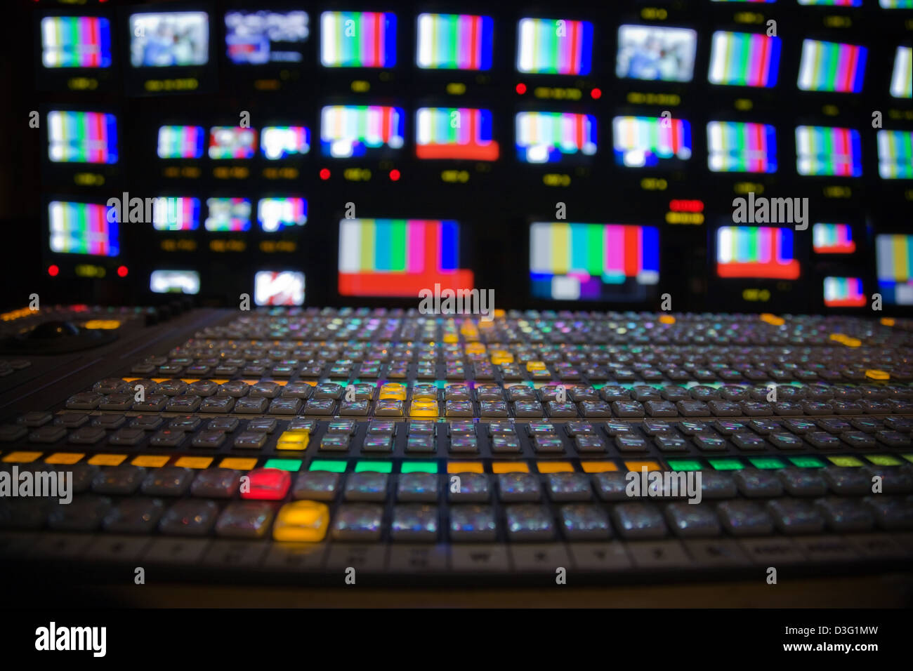 Wide shot of a Television gallery with foreground vision mixing panel and a large bank of TV screens in the background - Stock Image