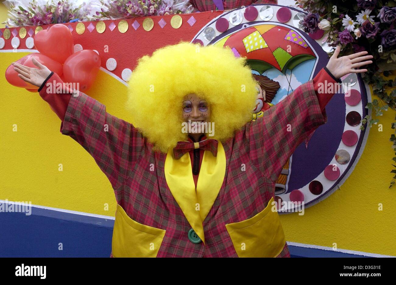 (dpa) - German top model Heidi Klum wears a carnival costume with a yellow wig and gestures a carnival greeting - Stock Image