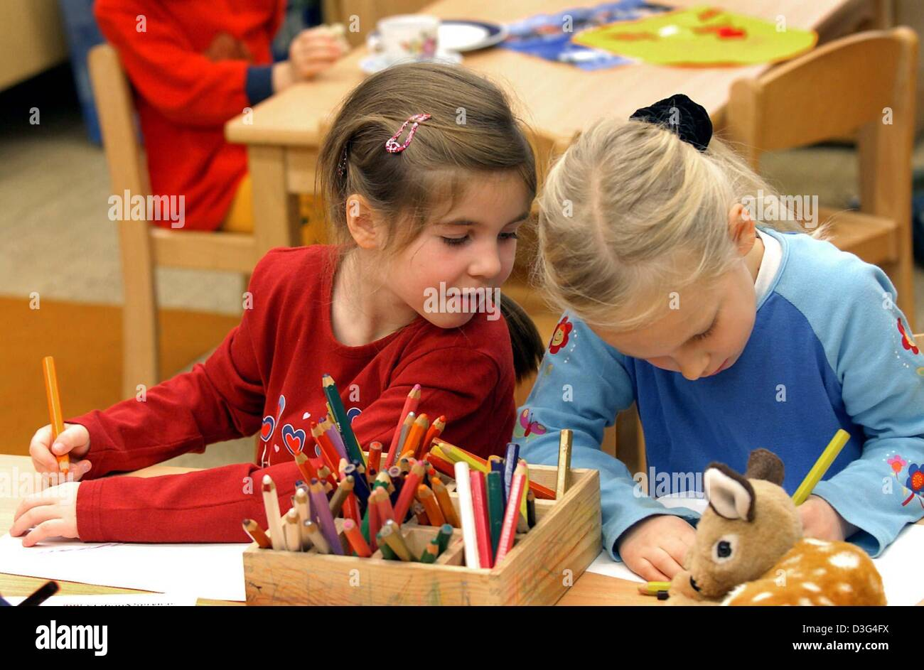 dpa Two girls are painting at the daycare kindergarten centre in