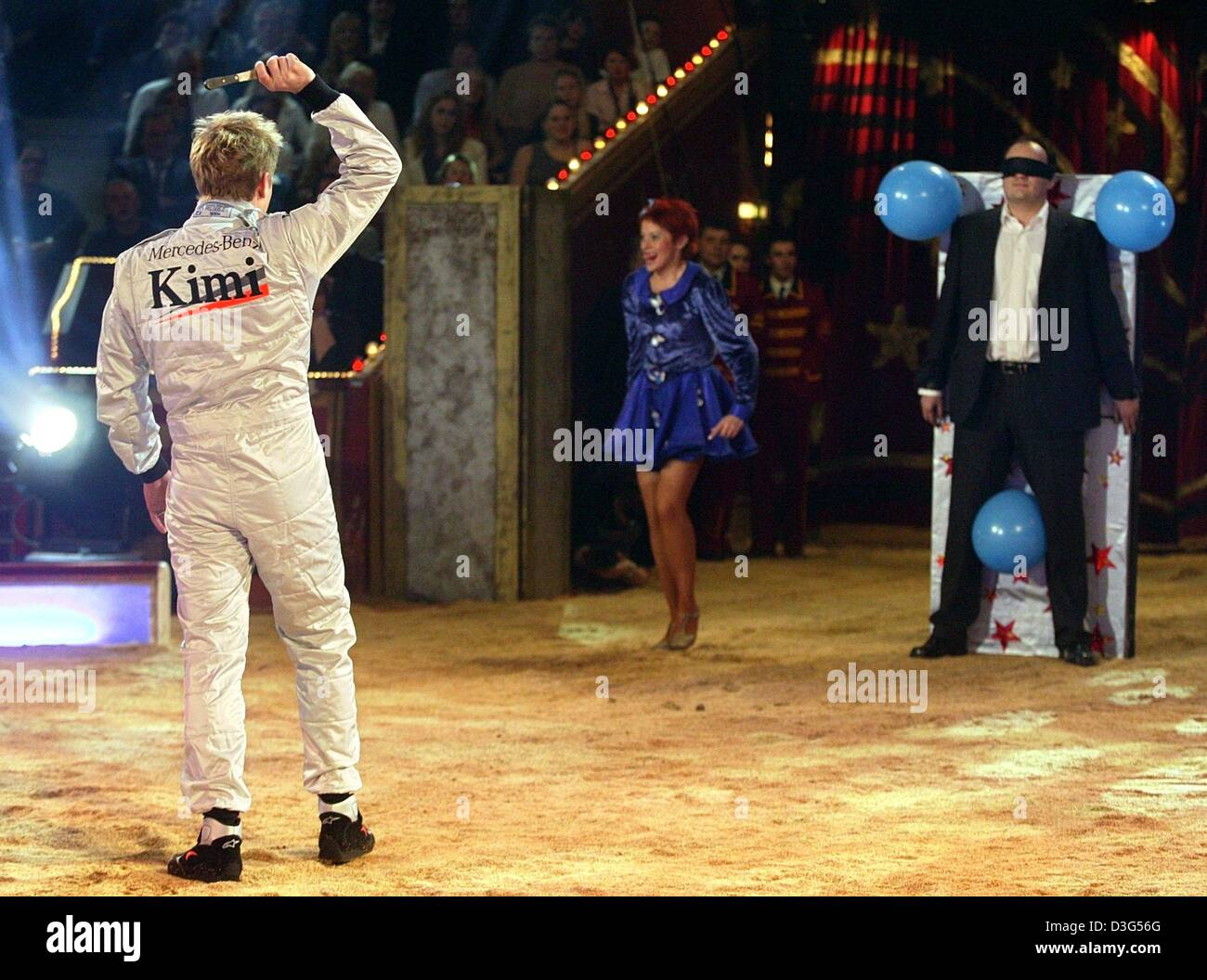 (dpa) - Finnish formula one pilot Kimi Raeikkoenen (L) performs as a knife thrower during the circus show 'stars - Stock Image