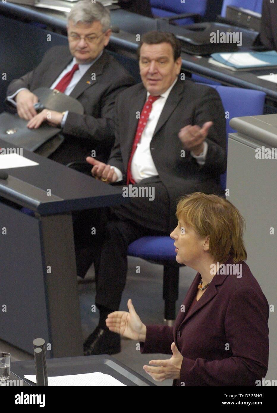 (dpa) - German Chancellor Gerhard Schroeder (C) and Foreign Minister and Vice Chancellor Joschka Fischer (L) listen to a speech by opposition leader Angela Merkel during a budget debate in the Bundestag in Berlin, 26 November 2003. Opposition parties accused Schroeder's government of bringing Germany to the 'brink of bankruptcy' by continuing heavy borrowing despite a flat economy. Stock Photo