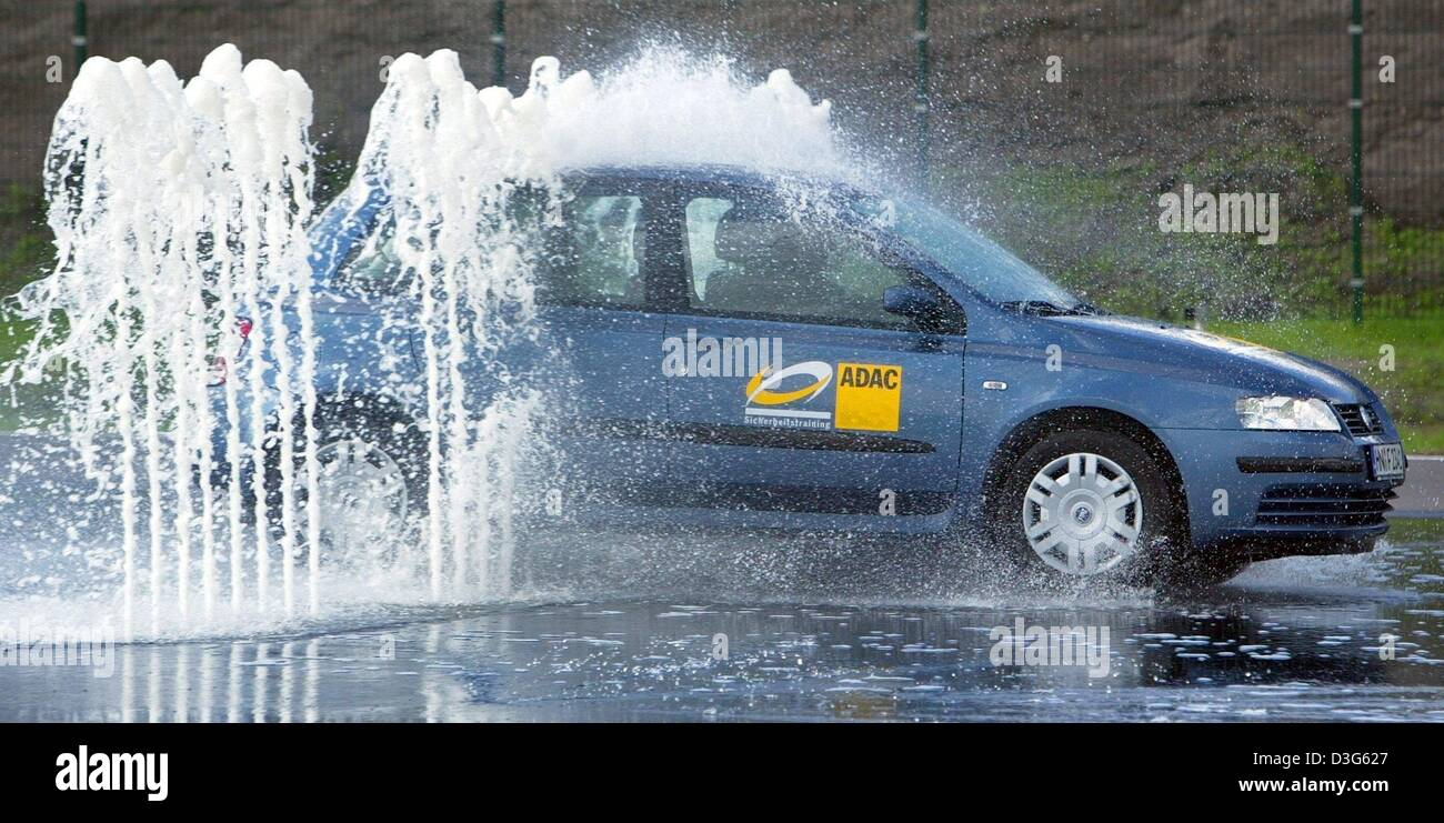 (dpa) - A passenger car drives through water fountains on a skidding course at the centre for driving safety of Stock Photo