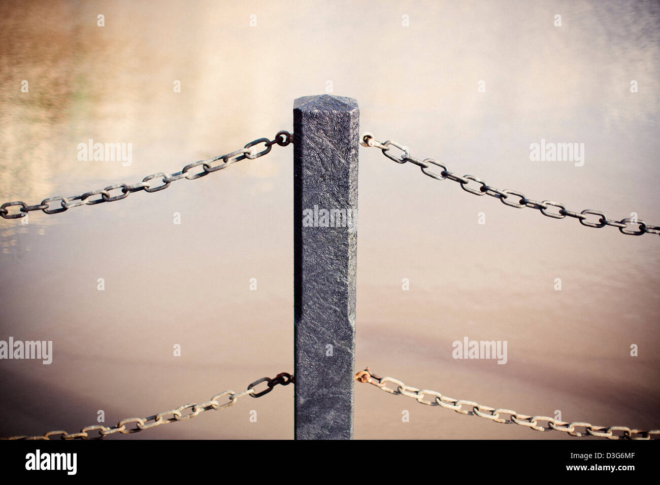 Railings made of recycled plastic material shot with a shallow depth of field next to a pool of water and a concrete - Stock Image