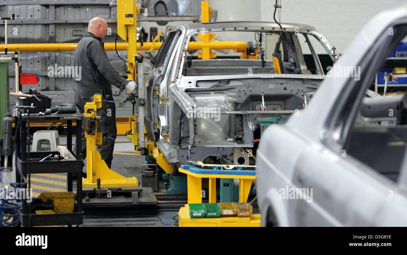 (dpa) - A worker in the production line of British carmaker Bentley during the assembly of hinges for the car door - Stock Image