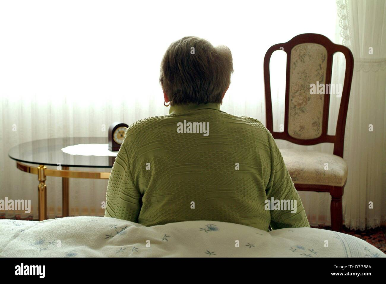 (dpa) - An older woman sits on a bed in her bedroom in Frankfurt, Germany, 19 October 2004. Stock Photo