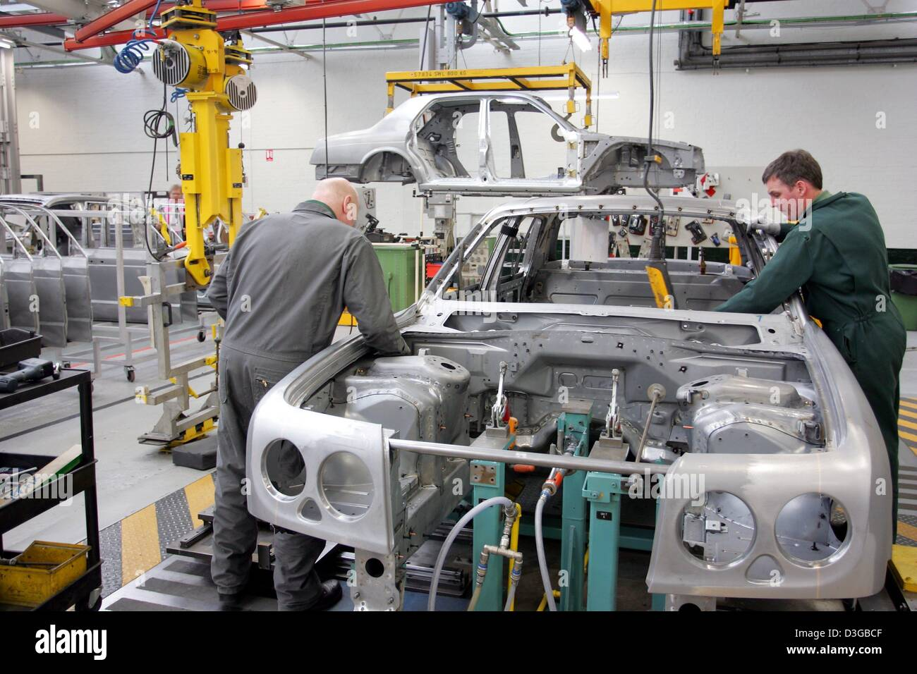 (dpa) - Two workers in the production line of British carmaker Bentley during the assembly of components on a body - Stock Image