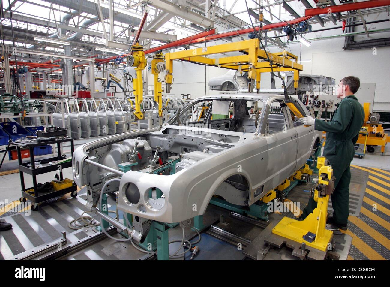 (dpa) - A worker in the production line of British carmaker Bentley during the assembly of components on a body - Stock Image
