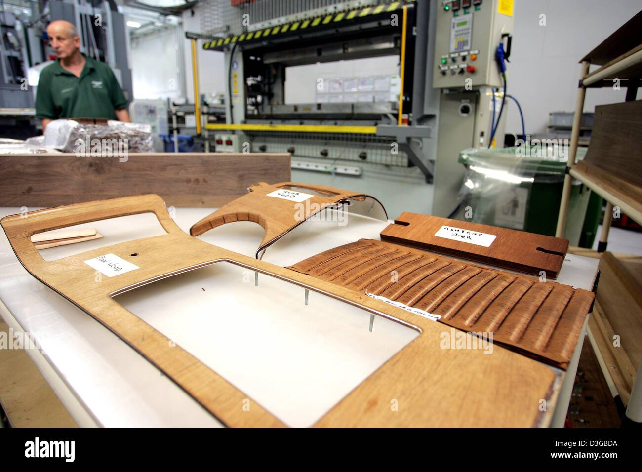 (dpa) - A worker in the production line of British carmaker Bentley Motors stands behind pieces of wood for the - Stock Image