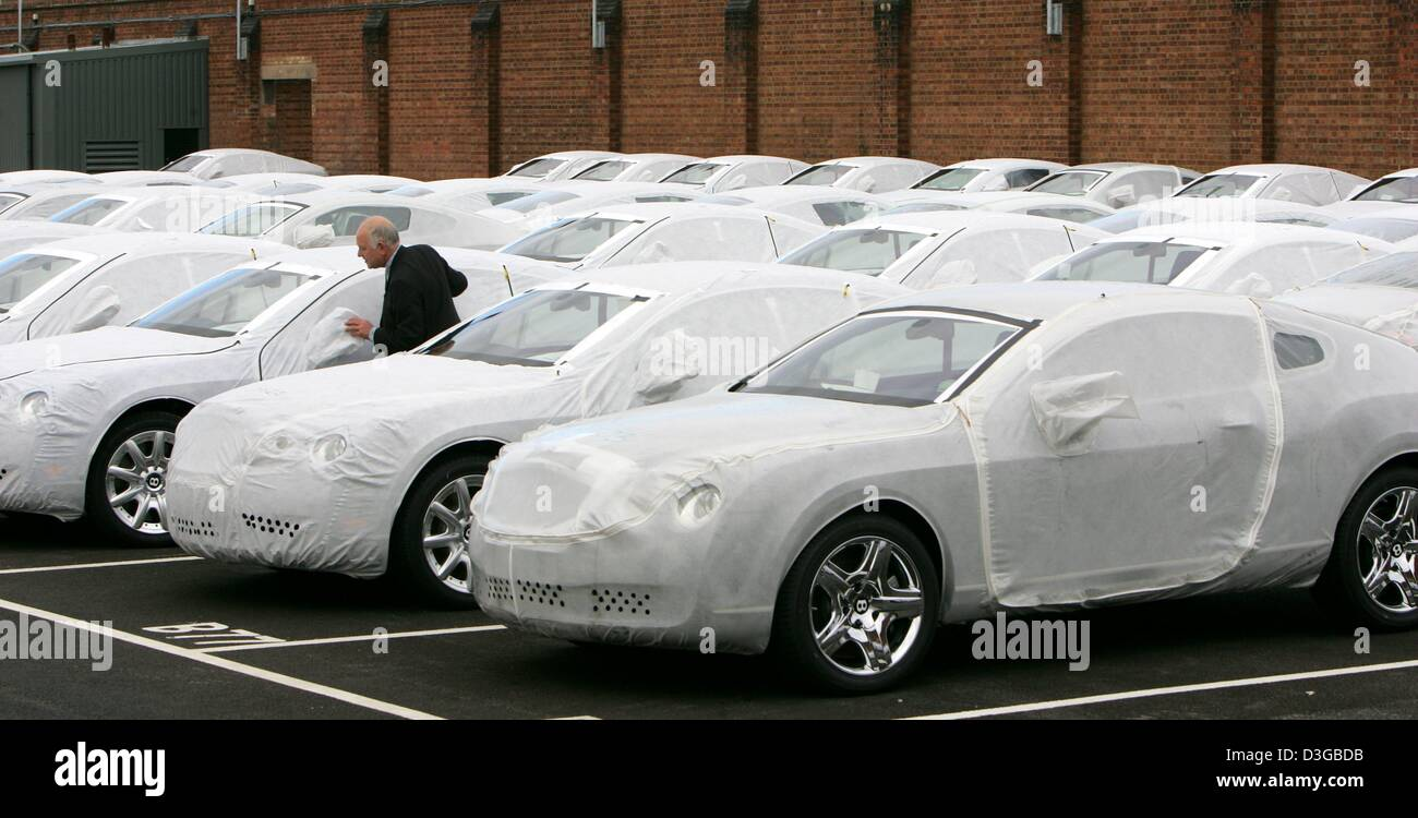 (dpa) - A worker of British carmaker Bentley Motors stands on the factory area between new cars that are protected - Stock Image