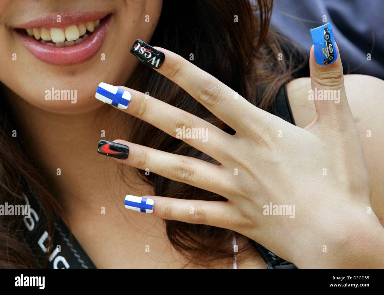 (dpa) - A Japanese fan of Finish formula one pilot Kimi Raeikkoenen shows her fingernails painted in the Finnish Stock Photo