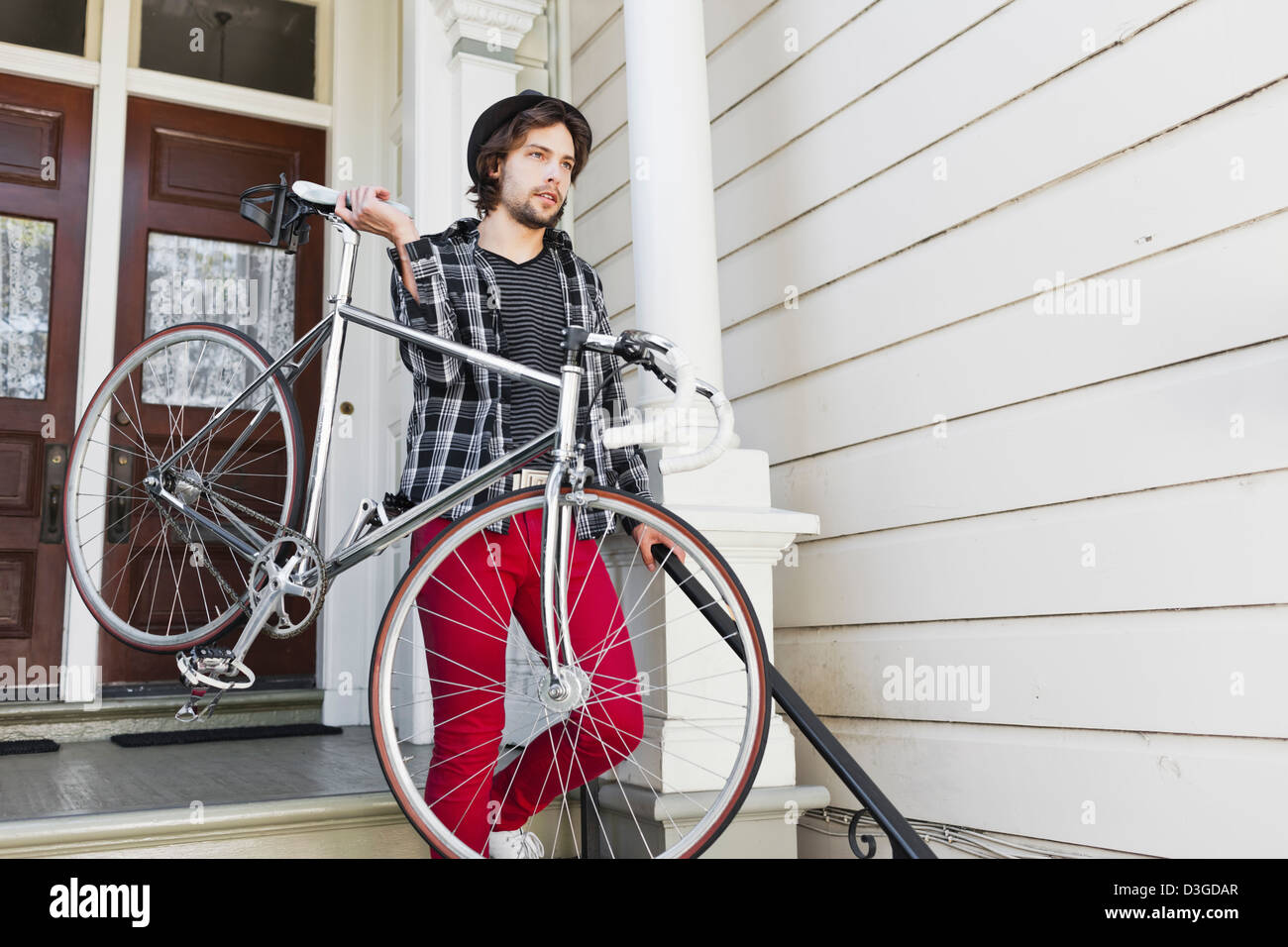 Hipsters and Beatniks - A young hipster man in tight jeans, plaid shirt, and hat about to leave home in his fixed - Stock Image