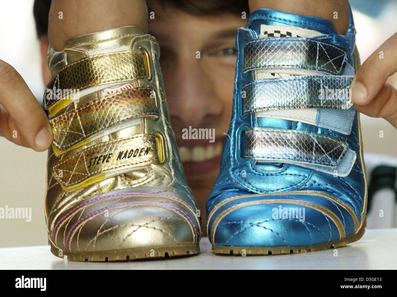 (dpa) - Joern is smiling as he opens the velcro fasteners of two flashy sneakers during a photocall at the GDS Sport - Stock Image