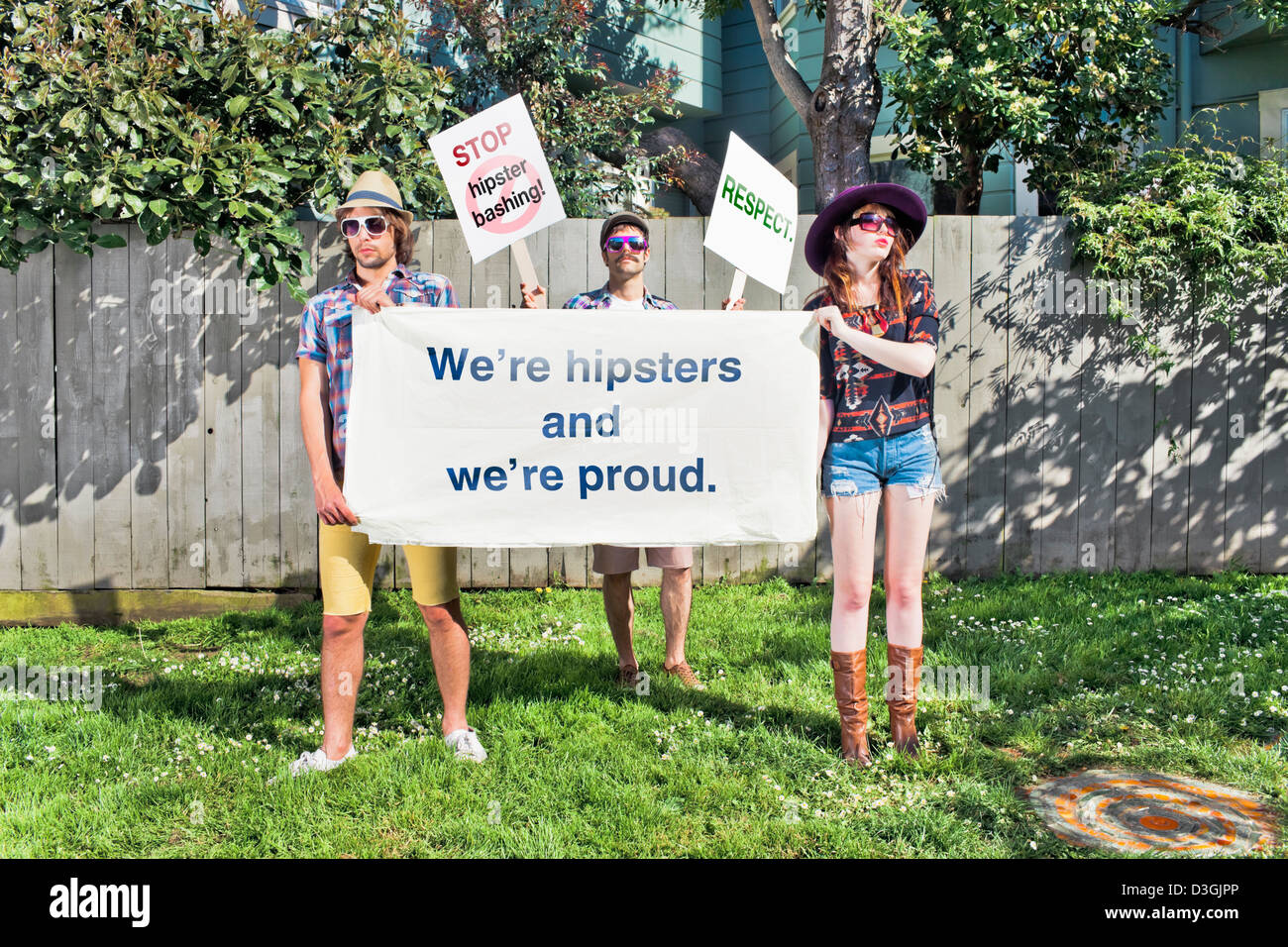 Hipsters and Beatniks - Three hipsters demonstrating against hipster-bashing, holding placards, signs, and banner - Stock Image