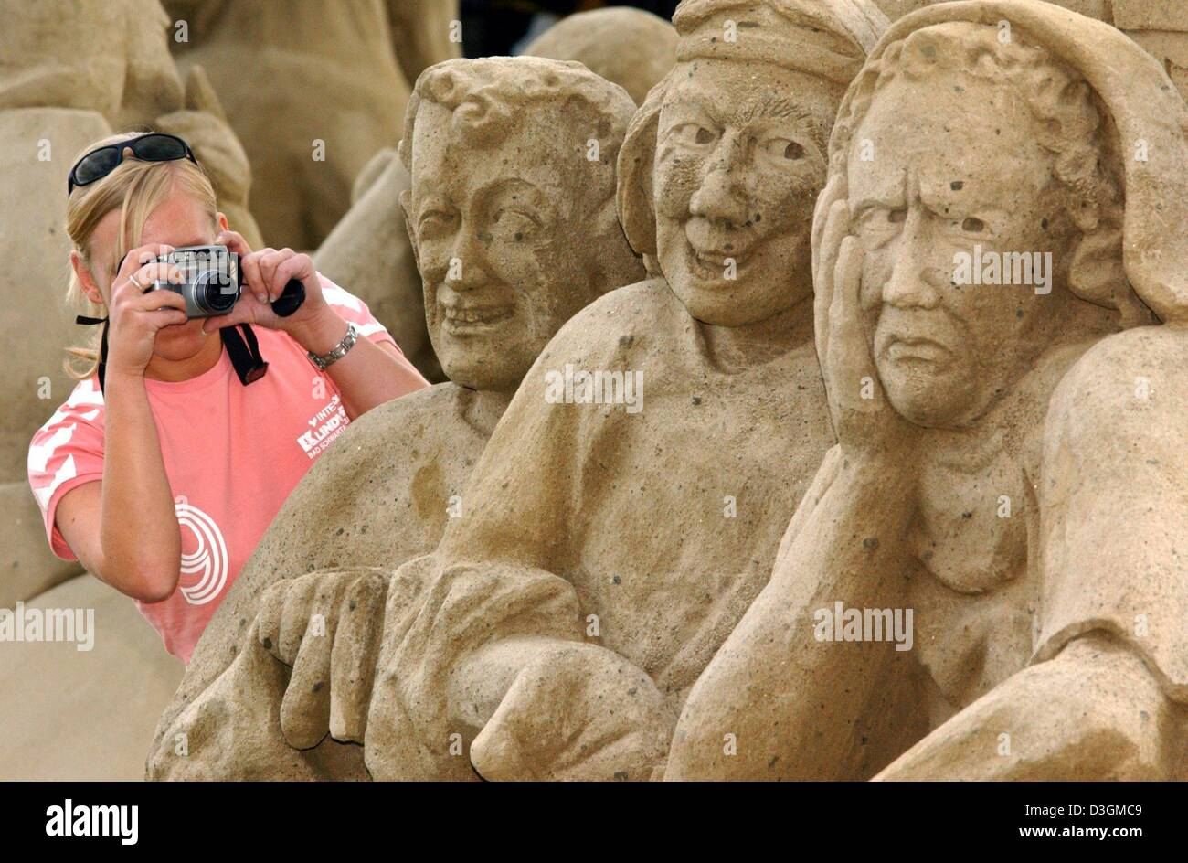 (dpa) - An employee takes a picture of three statues made of sand depicting the 'antique Nike Air trainers salesmen' Stock Photo