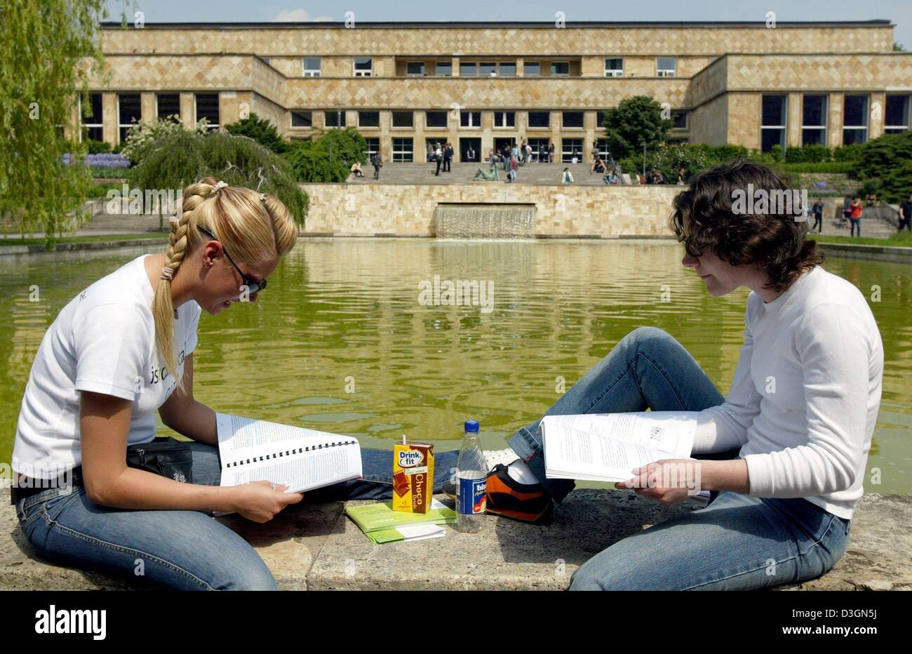 Students stduy during their lunch break in front of a pool on the campus of the Johann Wolfgang Goethe University Stock Photo