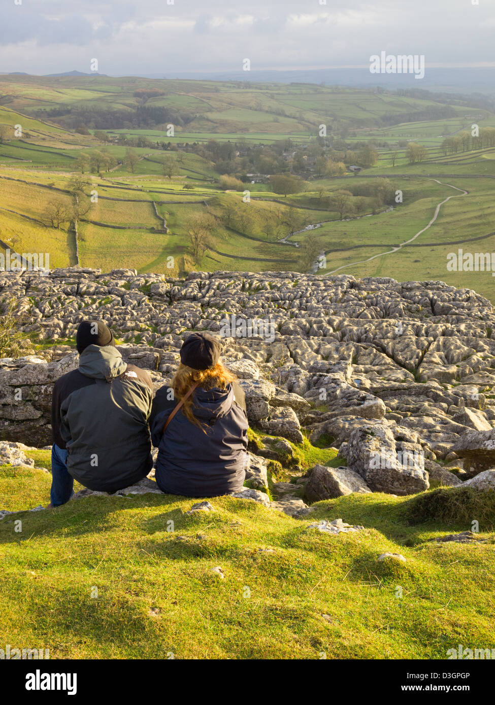 Couple looking out over Hetton Common from the top of Malham Cove in the Yorkshire Dales - Stock Image