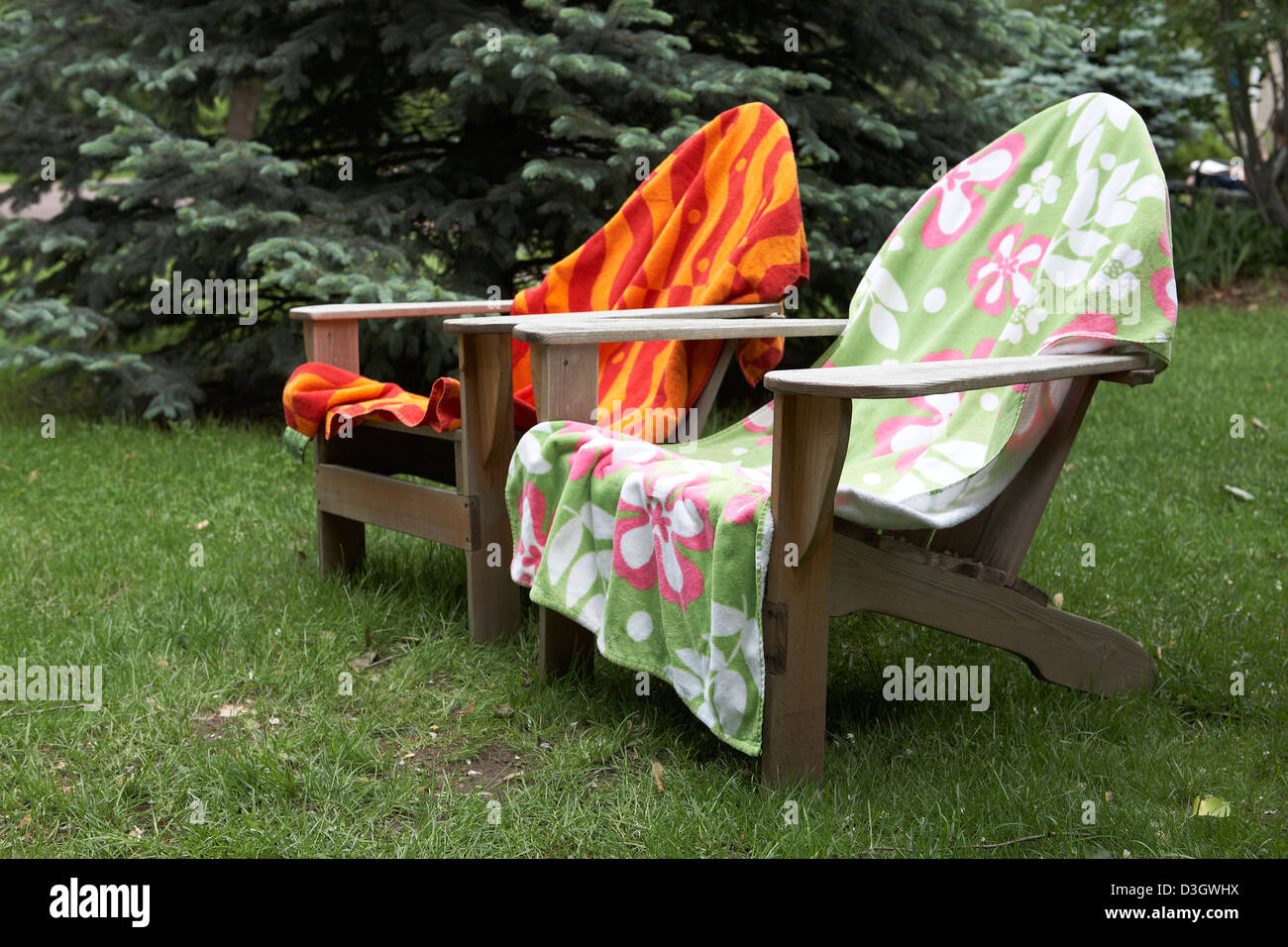 Colorful towels drying on Adirondack Chairs - Stock Image