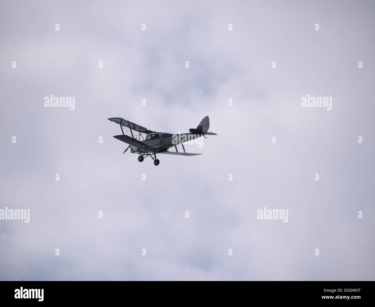 Vintage bi-plane flying over Quorn station just after dropping the commemorative poppies at great central railways - Stock Image