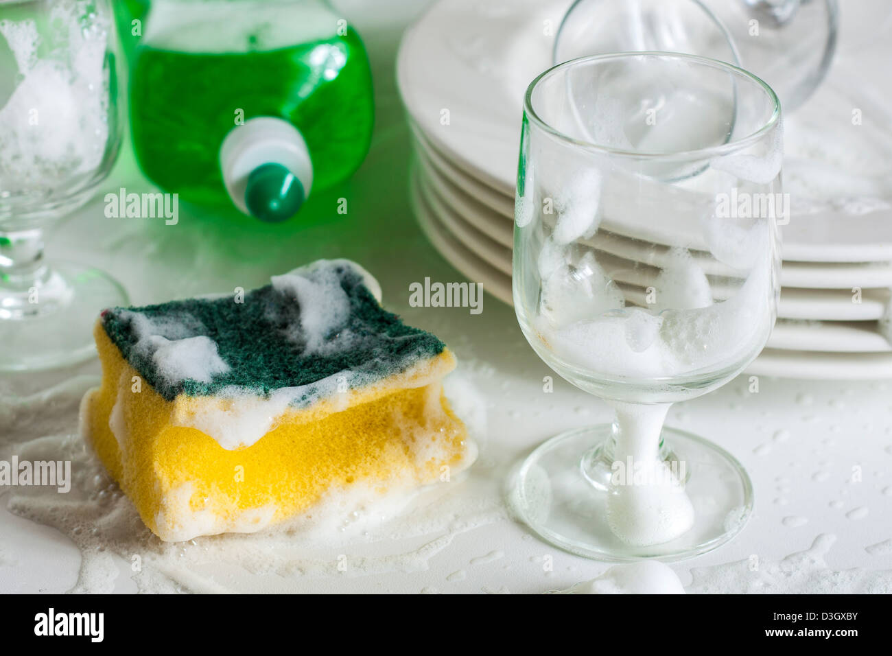 Washing glasses and plates with detergent and water - Stock Image
