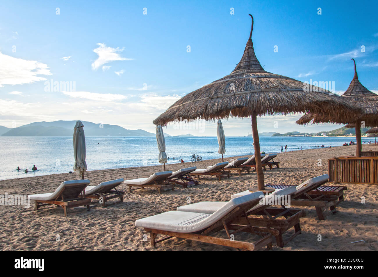 A row of relaxing beds and thatch umbrellas at a beach - Stock Image