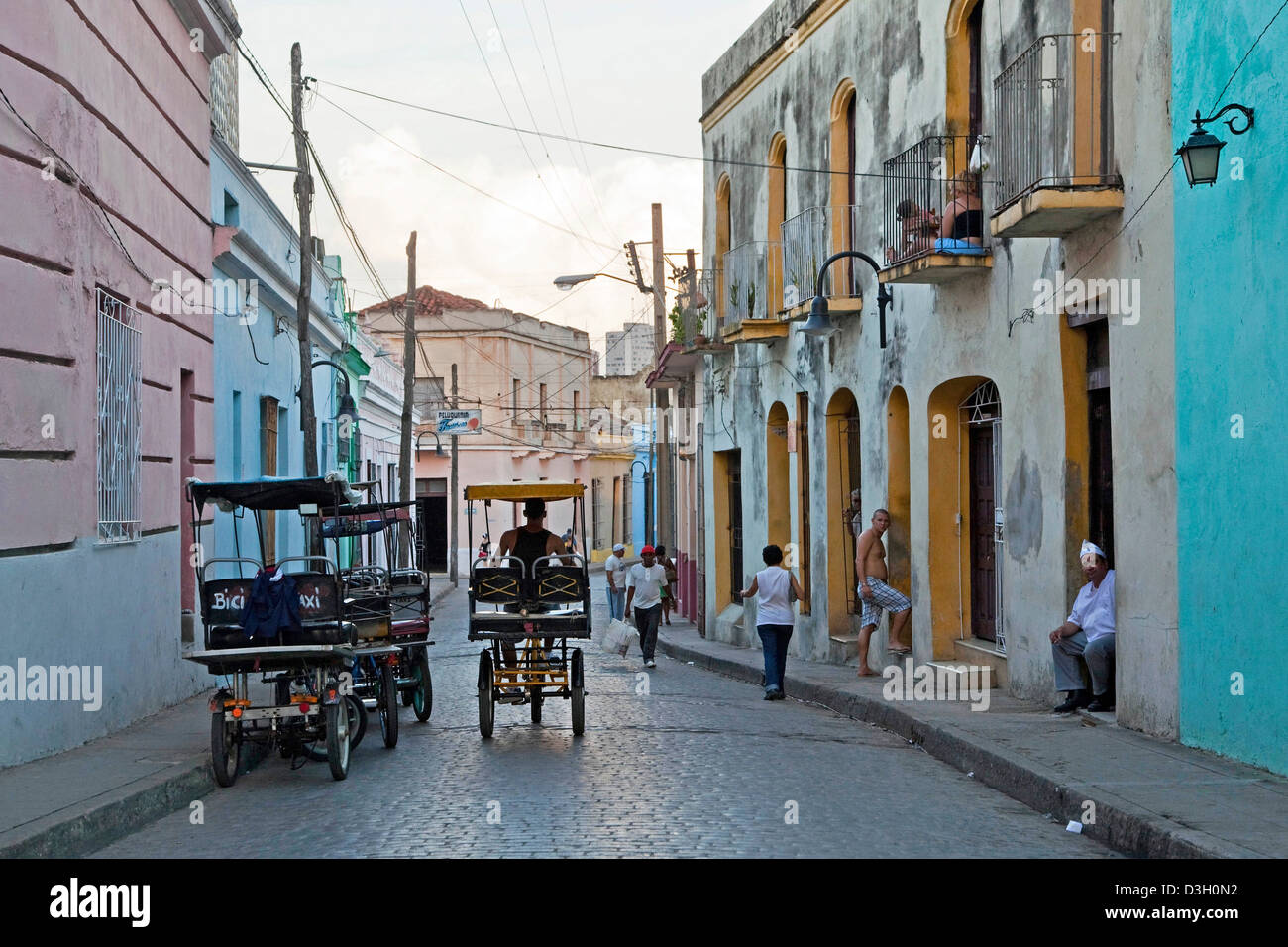 Street scene showing three-wheeled bicycle taxis in the city Camagüey, Cuba, Caribbean - Stock Image