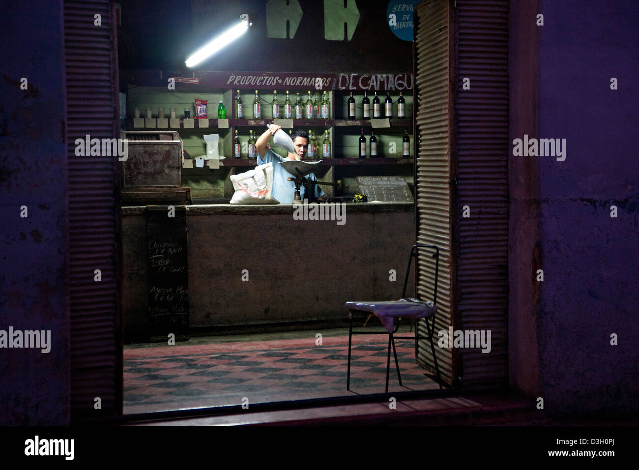 Shopkeeper behind counter of Cuban state shop in the city Camagüey, Cuba, Caribbean - Stock Image