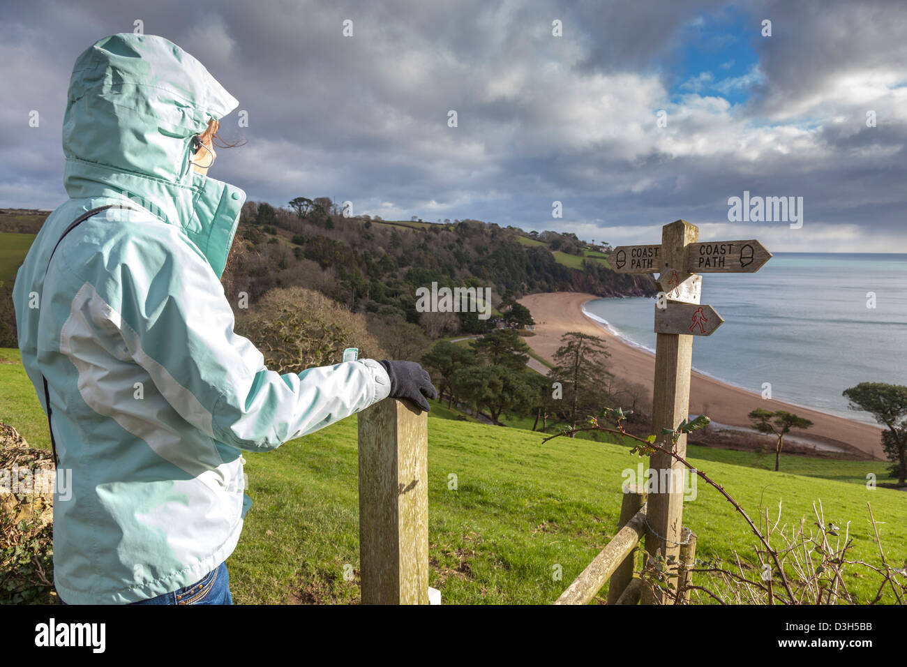 A girl dressed for the winter, enjoys the view over Blackpool Sands, Devon, during a walk along the south west coastal - Stock Image