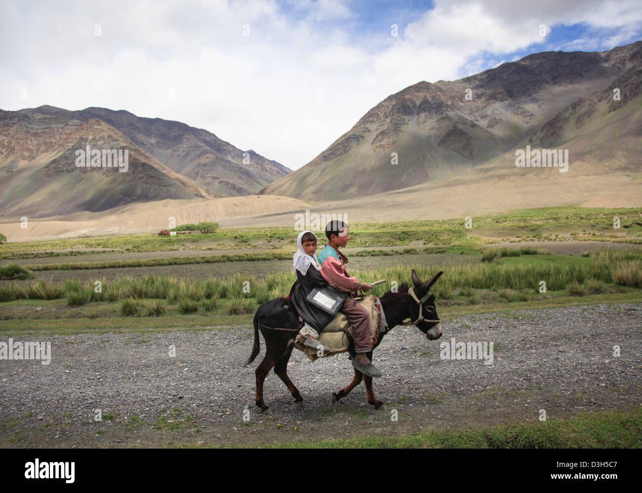 school children wakhan headscarf girl donkey - Stock Image
