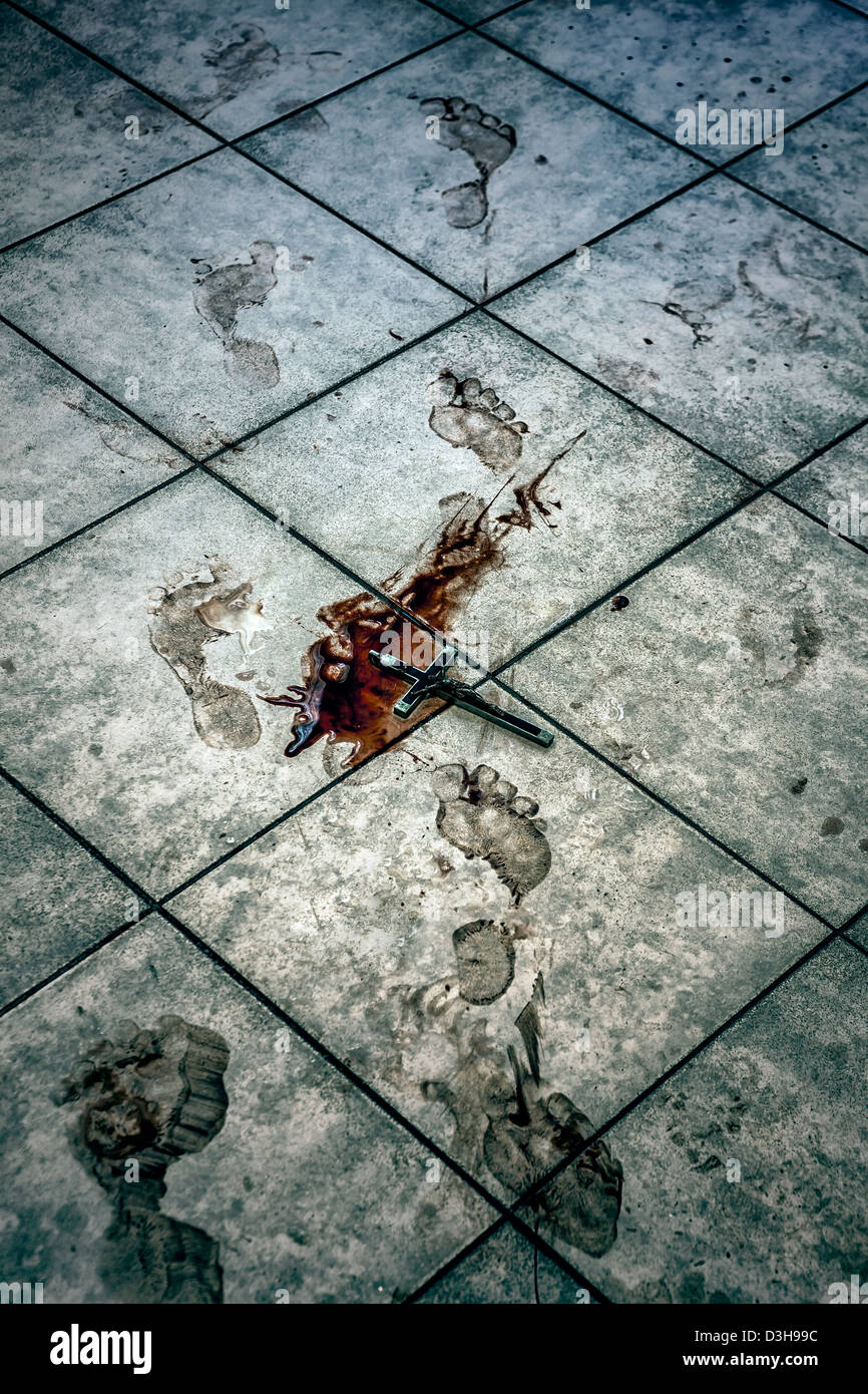 bloody foot prints and a crucifix in a pool of blood on a bathroom floor - Stock Image