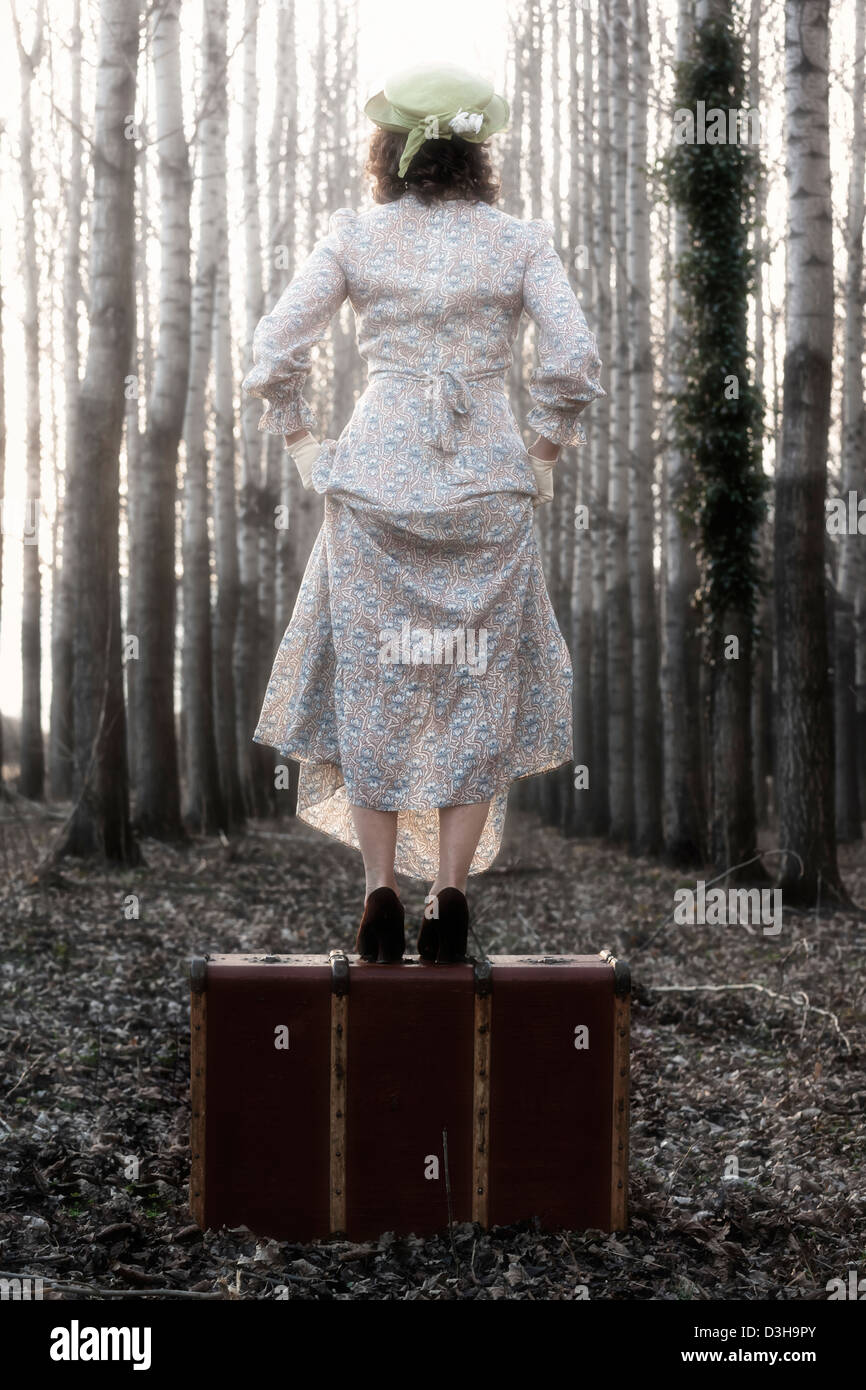 a woman in a floral vintage dress is standing on an old suitcase Stock Photo