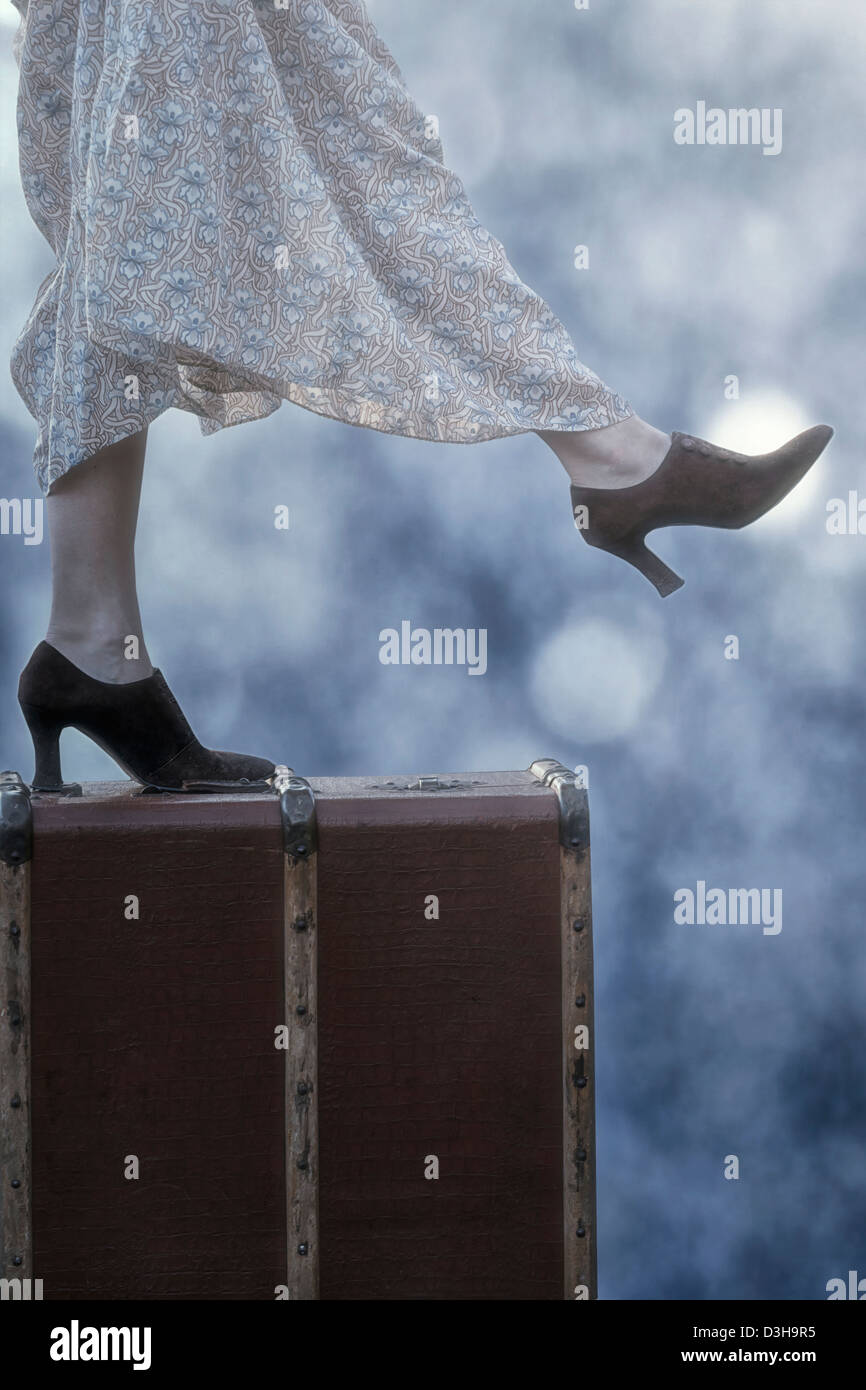 a woman in a floral vintage dress is standing on an old suitcase - Stock Image