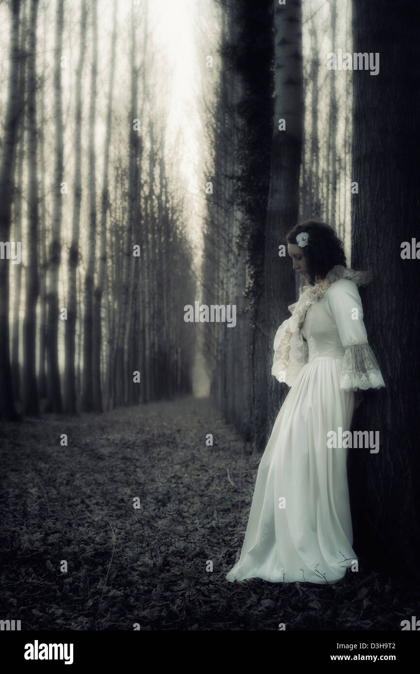 a woman in a dark forest - Stock Image