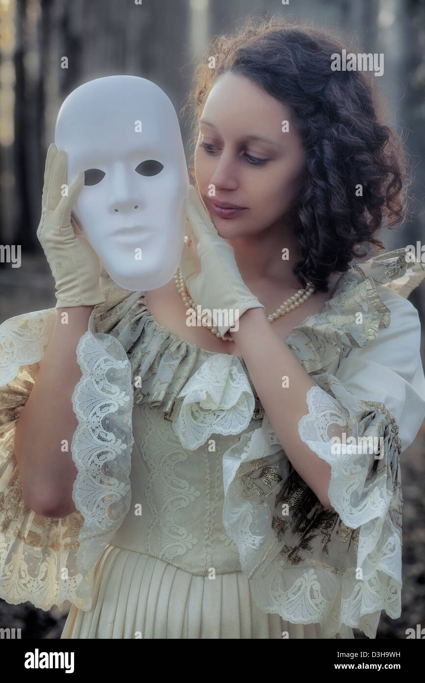 a woman in a period dress is holding a white mask - Stock Image
