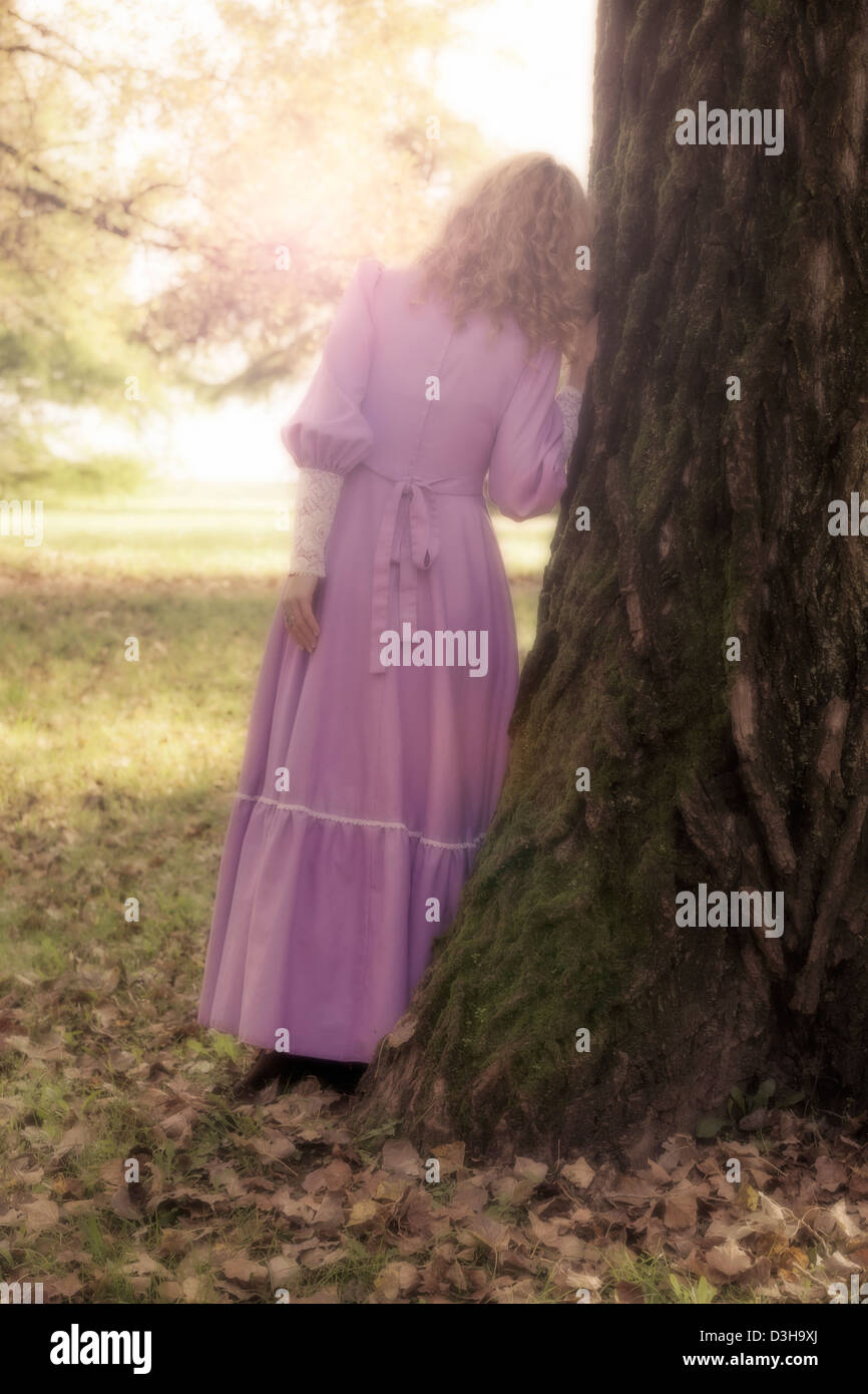 a woman in a pink dress is leaning against a trunk - Stock Image