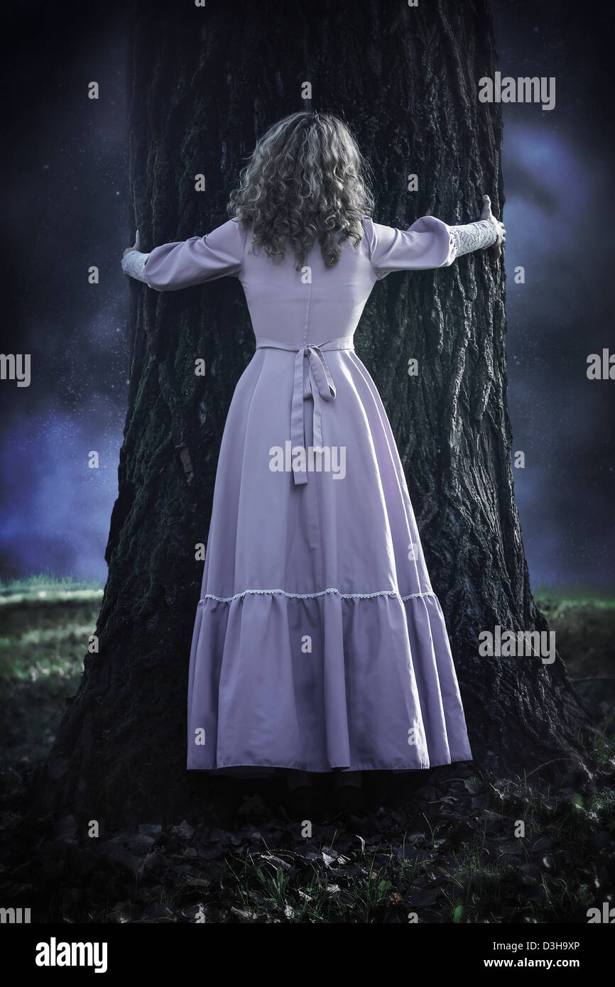a woman in a pink dress is hugging a trunk - Stock Image