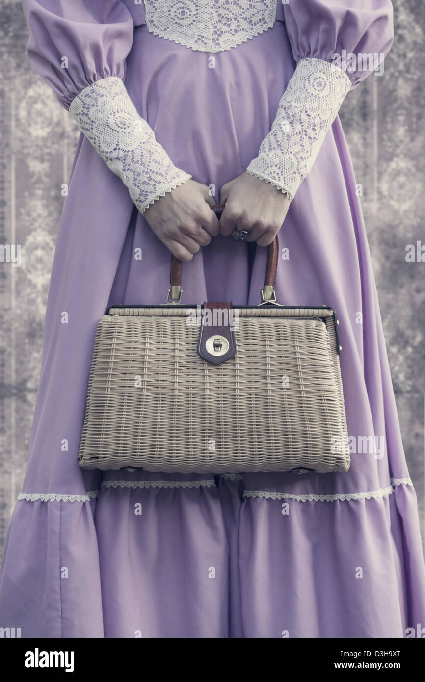 a woman in a pink dress with a vintage handbag - Stock Image