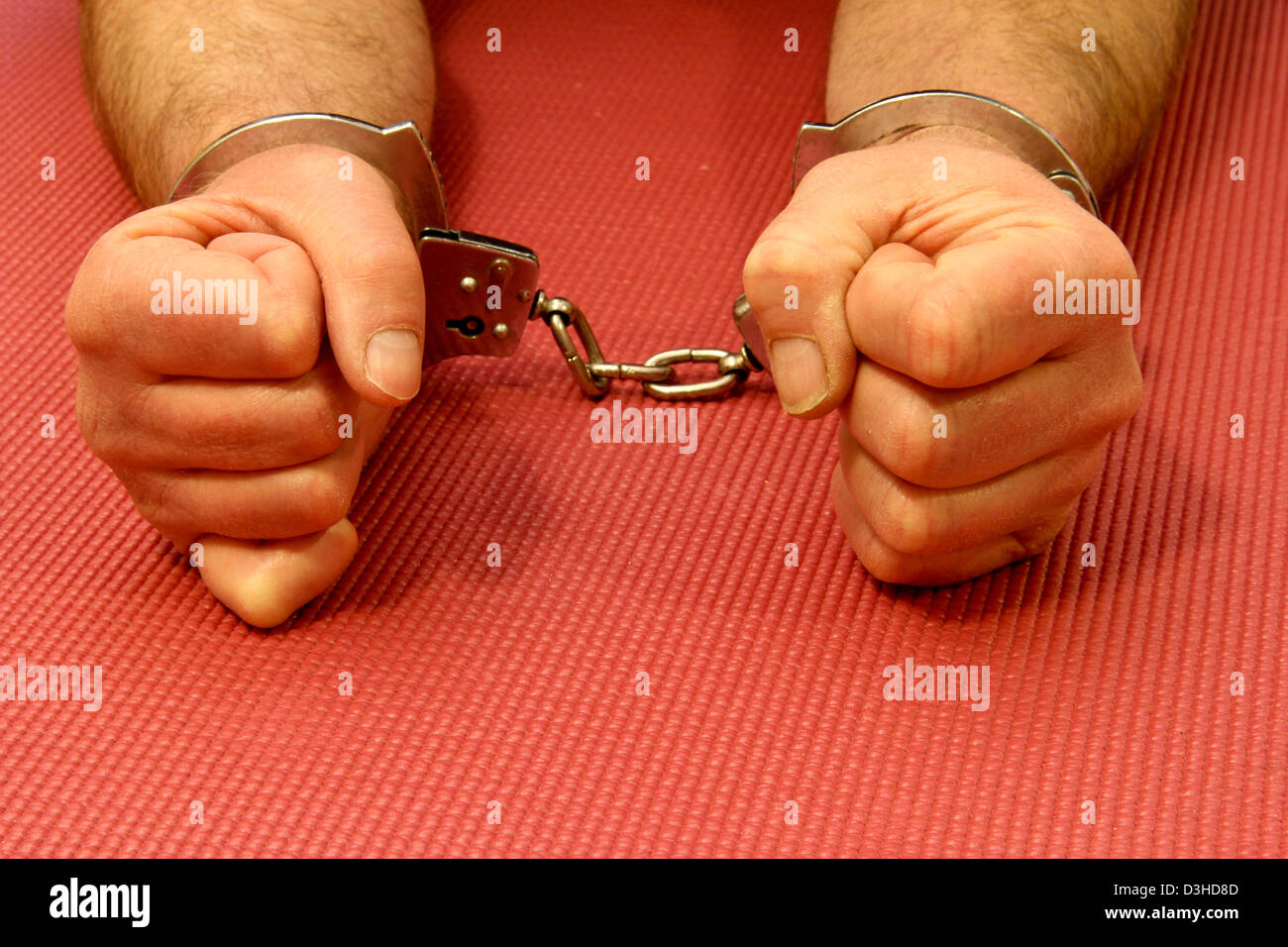 handcuffs on a prisoners wrist over a rubber mat background - Stock Image