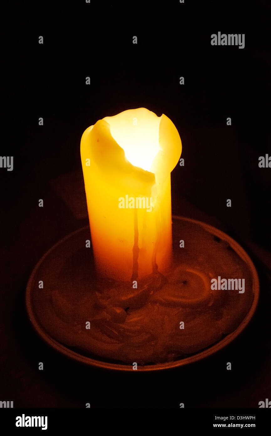 Overflowing yellow candle on a plate in darkness. - Stock Image