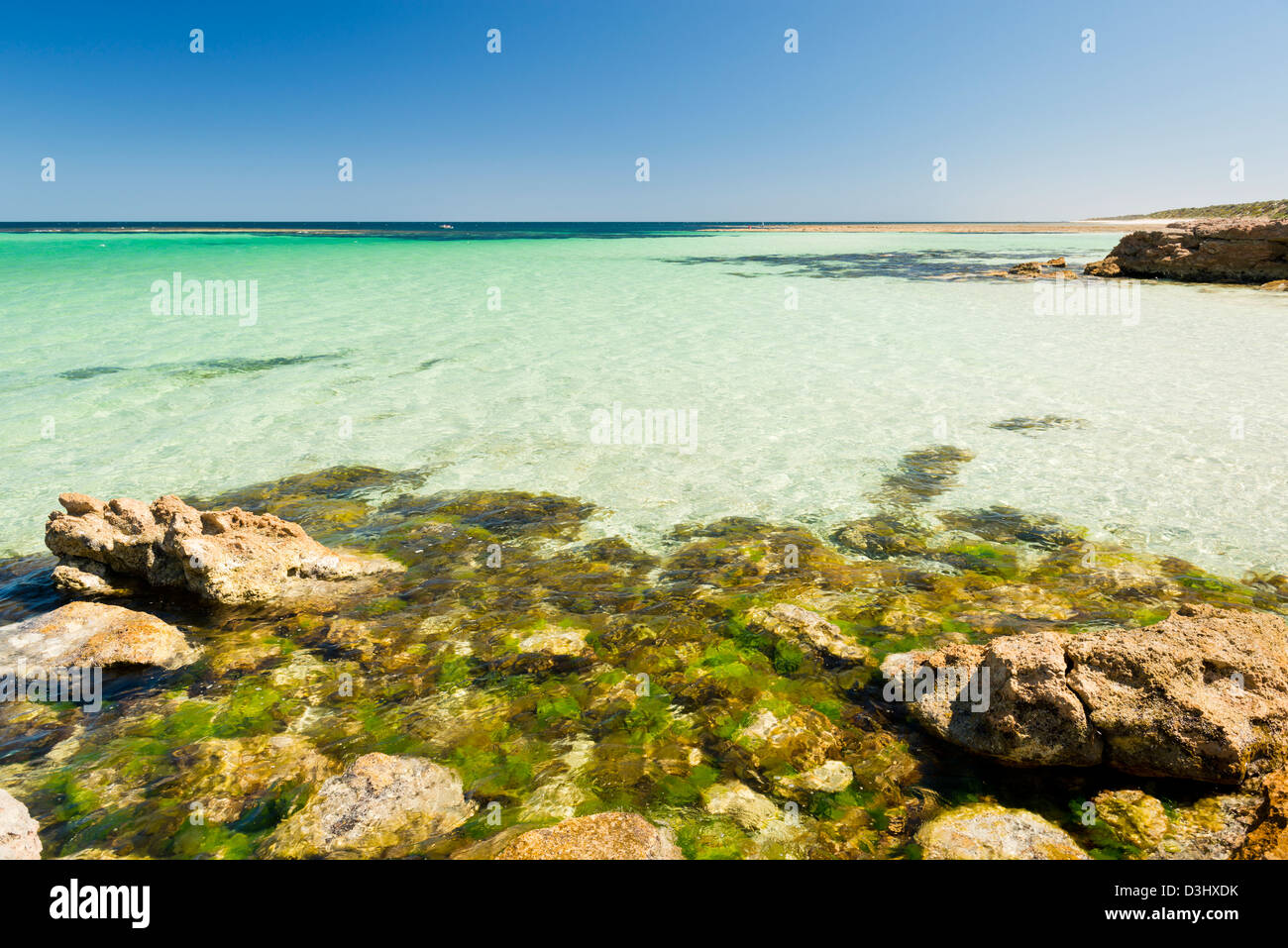 Crystal clear waters with amazing colors along the rocky coast - Stock Image