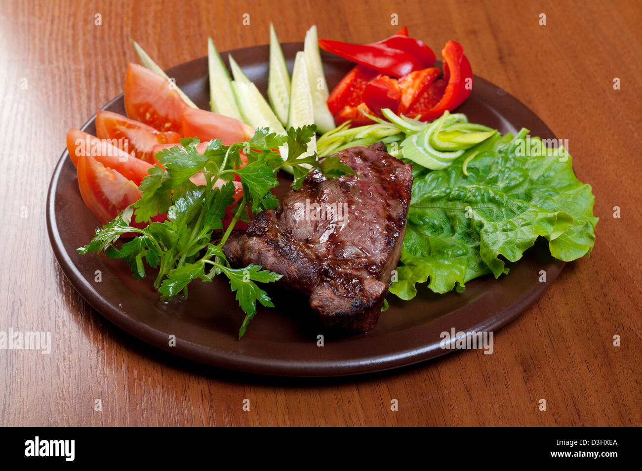 Grilled beef on white plate with vegetable - Stock Image
