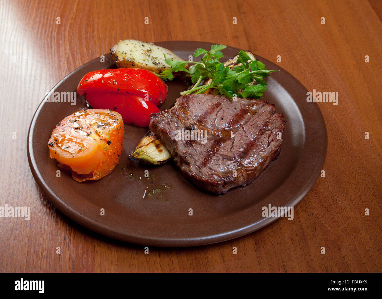 Grilled beef on white plate with vegetable . Close-up - Stock Image