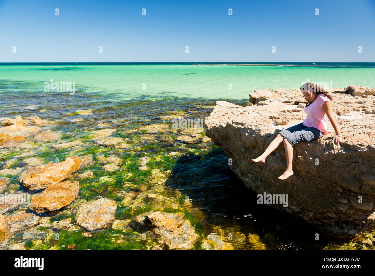 Young woman tourist enjoys the amazing water and rocks - Stock Image