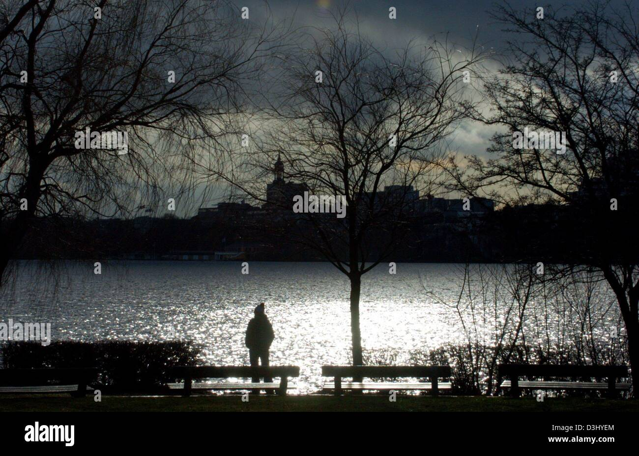 (dpa) - Dark clouds move slowly across the sky as a stroller stands at the bank of the sparkling river Alster looking - Stock Image