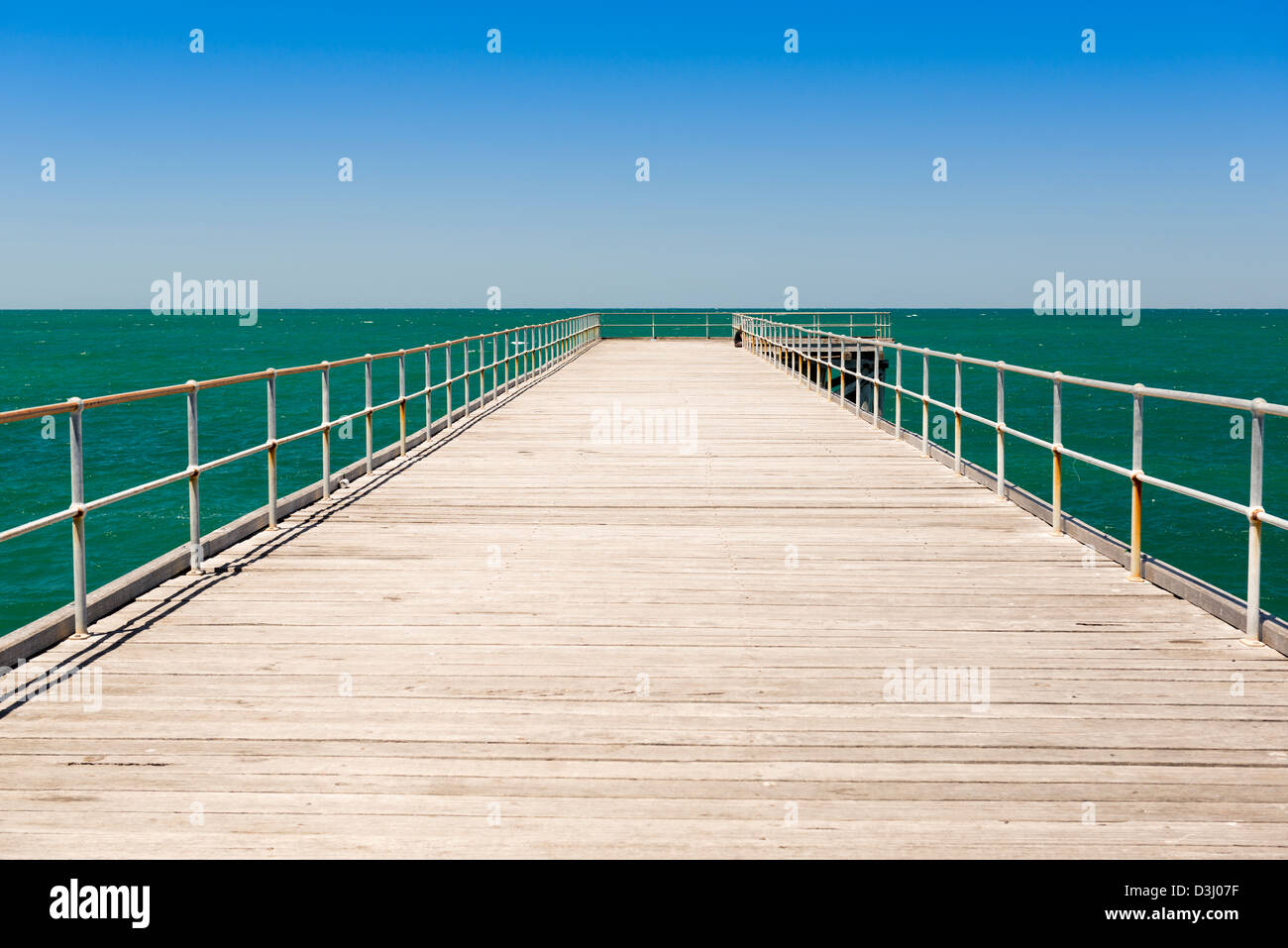 Long wooden jetty stretches out into clear water at Stenhouse Bay, South Australia - Stock Image