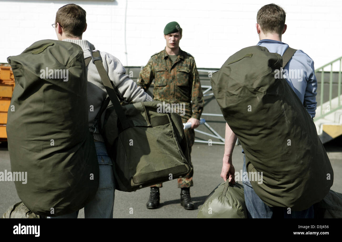 (dpa) - Conscripts still in civilian dress carry their new uniforms in green bags and report to their instructor: Stock Photo